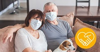 A couple wearing facemasks sitting on couch with dog on their laps.