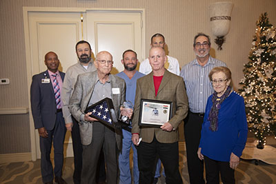 Dr. Adams with colleagues, flag andaward