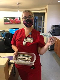 Palm Bay Hospital Associate, Angel, holding box of hand-made facemasks.