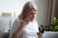 Woman sitting on couch looking at cell phone with hand in air in shock about what she is seeing.