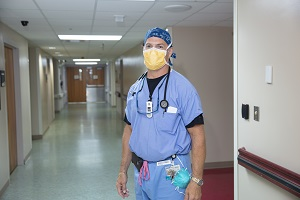 Healthcare provider wearing mask in hallway alone.