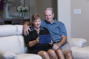 Couple sitting on couch with iPad making a virtual visit