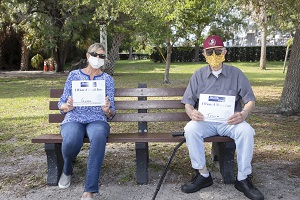 Couple sitting on park bench two feet apart, each holding a Health First logo sign that reads I Wear A Mask For. Woman sign reads Gene. Man sign reads Tricia.